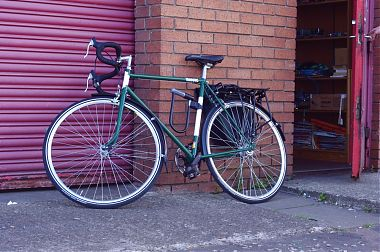 Shiny and new looking bike, leaning against door of Commonwheel project