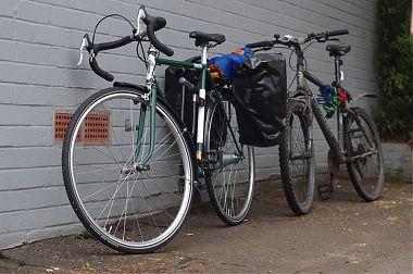 Green Sun Racer leaned against a wall, mountain bike behind it