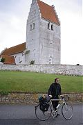 Young man with bike in front of white church.