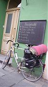 bike, leaned against sign offering all sorts of sweet snacks